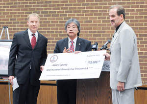 Jim Cheng, Virginia Secretary of Commerce and Trade, presents a $175,00 Governor's Opportunity Fund check to Jim Adams (right), chairman of the Henry County Board of Supervisors, and Steve Phillips (left), CEO of Commonwealth Laminating & Coating.